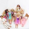 Lot de 10 barbies, un ken, un bébé, vêtements Barbie et accessoires