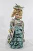 Petite poupée en porcelaine robe verte